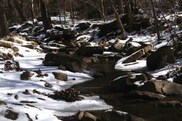 snow capped creek rocks by gate