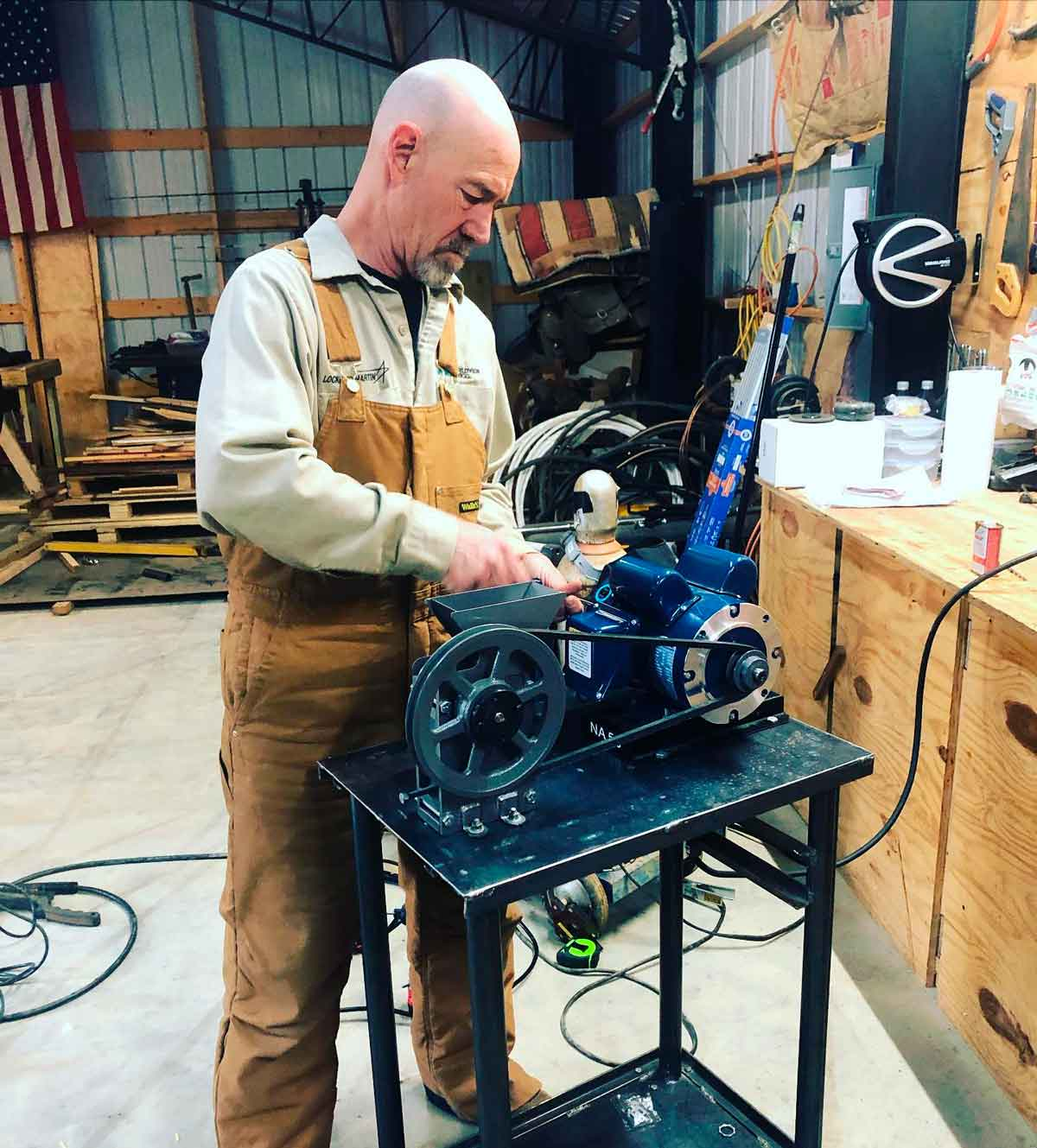 Rob putting the rock crusher together on the cart he fabricated from metal and pipe.